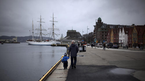 A man walks with a child near the marina in downtown Bergen, southwestern Norway, March 20, 2012.