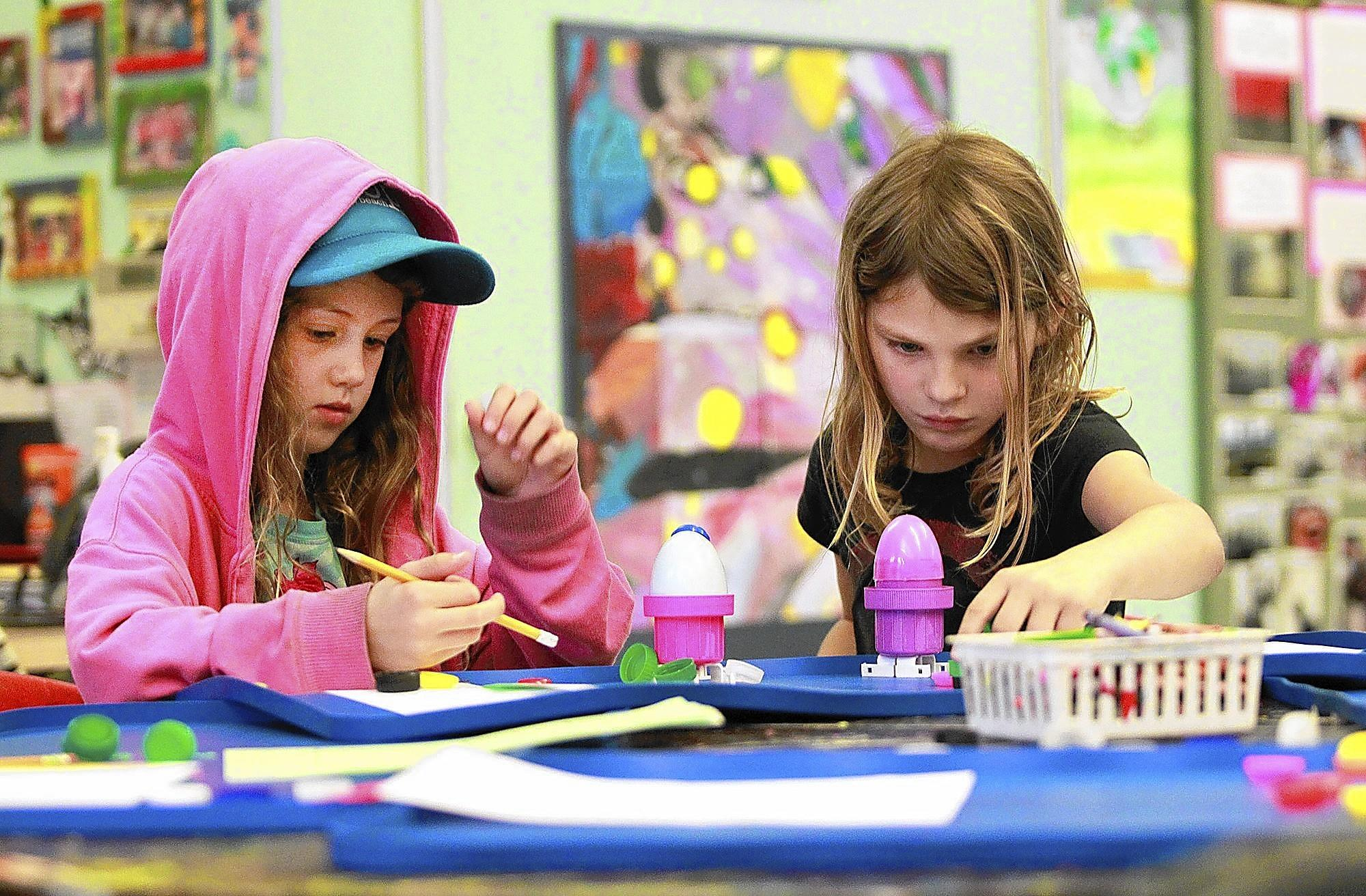 "Izzy Gray, left, and Mia Pehar build their ""plastikobots"" during the Child Creativity Lab with artist Claudio Garzon at the Boys and Girls Club of Laguna Beach."