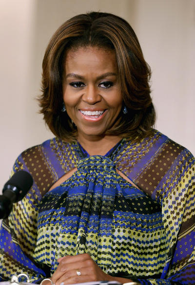 "First Lady Michelle Obama, accompanied by singers, from left to right, Melissa Etheridge, Janelle Monáe, and Patti LaBelle as part of the ""In Performance at the White House"" series. The first lady wore this multicolored striped dress and her soft hairstyle brought out the blonde highlights in her hair."