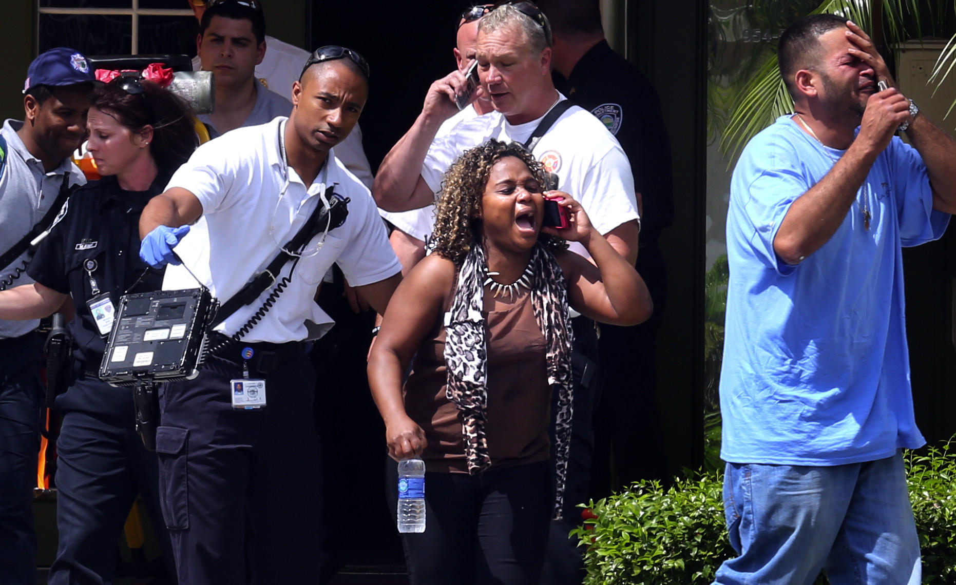 A mother is led from the scene after two toddlers were pulled from a swimming pool in Sunrise.