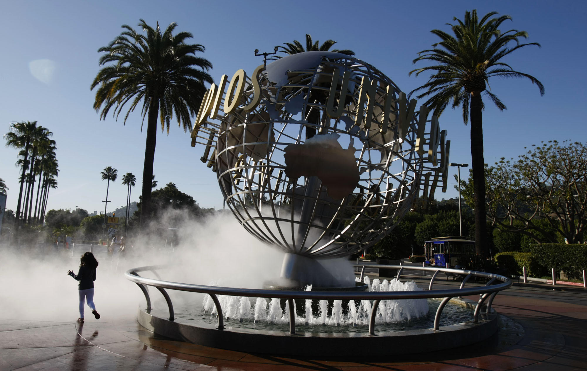 A girl runs through the spray at the entrance of Universal Studios Hollywood. Construction for a new Universal Studios park in Beijing will begin later this year.