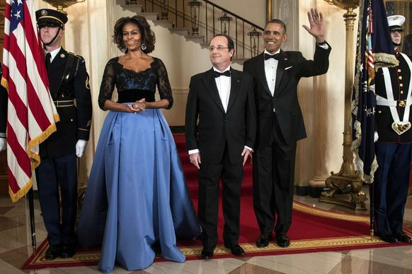First Lady Michelle Obama, French President Francois Hollande and President Obama at a White House state dinner for Hollande's visit to the United States. The first lady wore a blue Carolina Herrera gown with a sheer black top featuring floral details.
