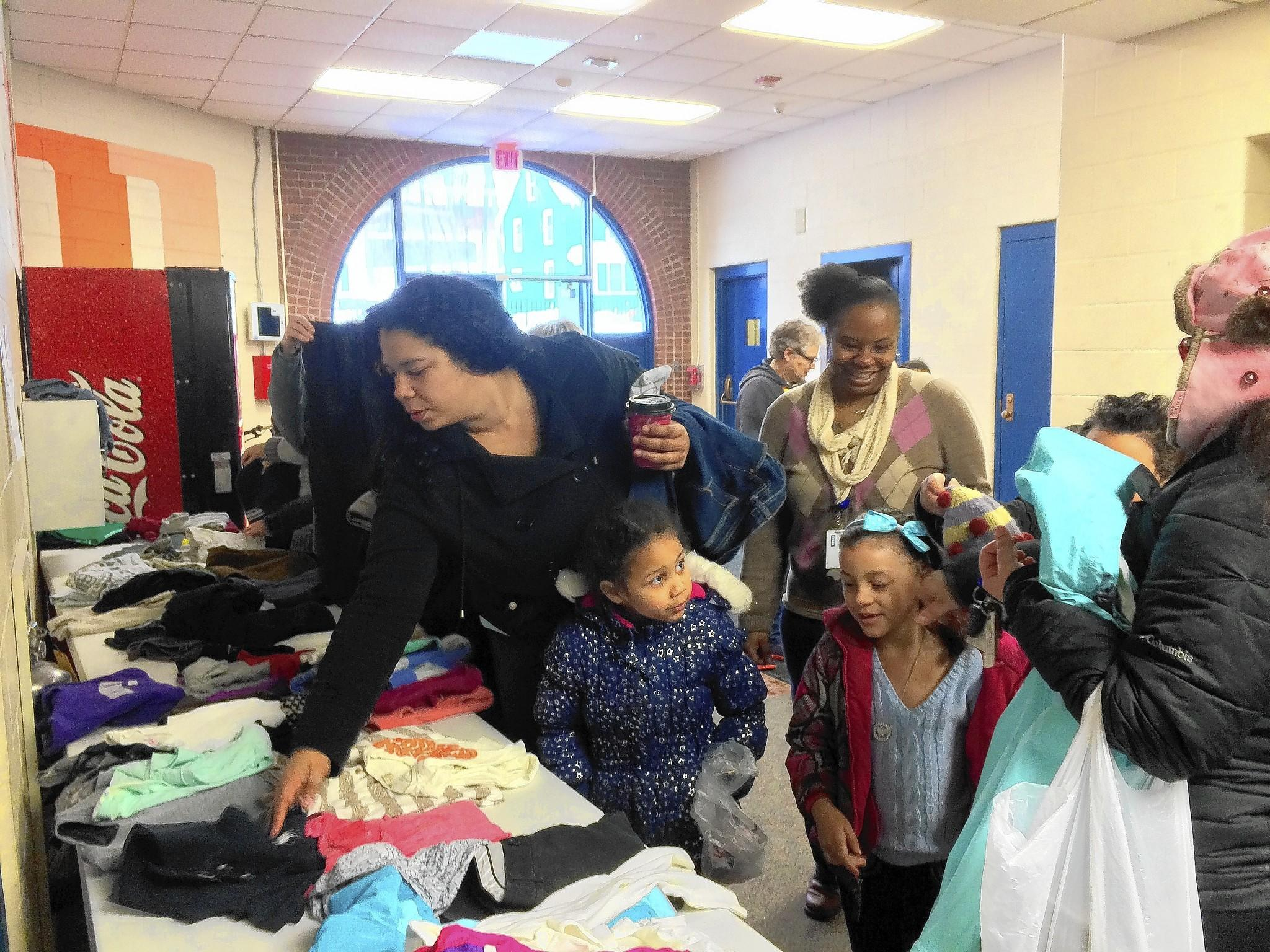 Tasha Armstrong, left, looks through items of clothing donated for the Washington Wears event with her daughter Makayla Rivera.
