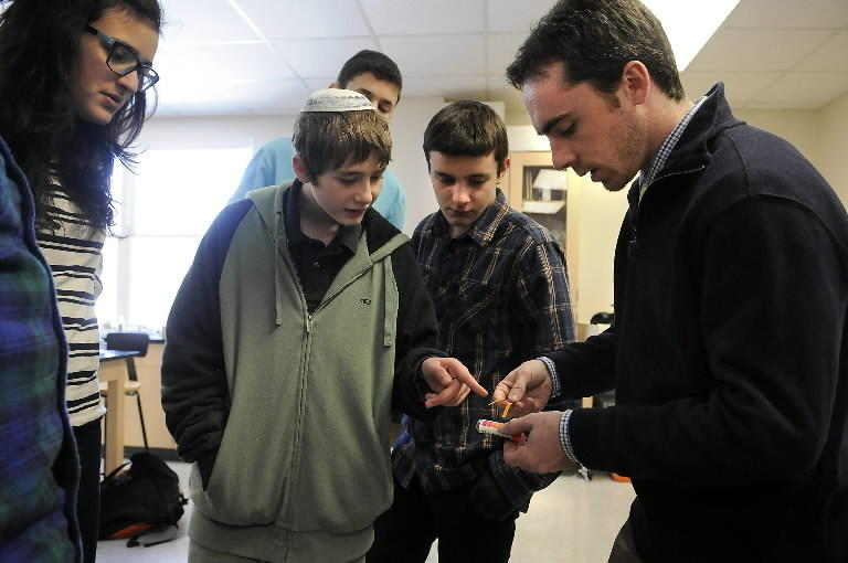Natan Glahn, 14, points to the PH test strips teacher Pat Collins is holding as students from Hebrew High School of New England in West Hartford collaborate with students in Israel on a science project studying rivers and their effects on the ecosystem. HHNE is one of four pilot schools selected from throughout North America to be part of a unique science partnership with Pearson, the world's largest education company, World ORT, the world's largest Jewish education and vocational training non-governmental organization, and Israel's Ministry of Education. Freshman physical science students will be working in pairs over Skype with the students in Israel. Miriam Edry, 14, Gabriel Katz, 14 (behind Glahn) and Benjamin Snyder, 14, are also pictured.