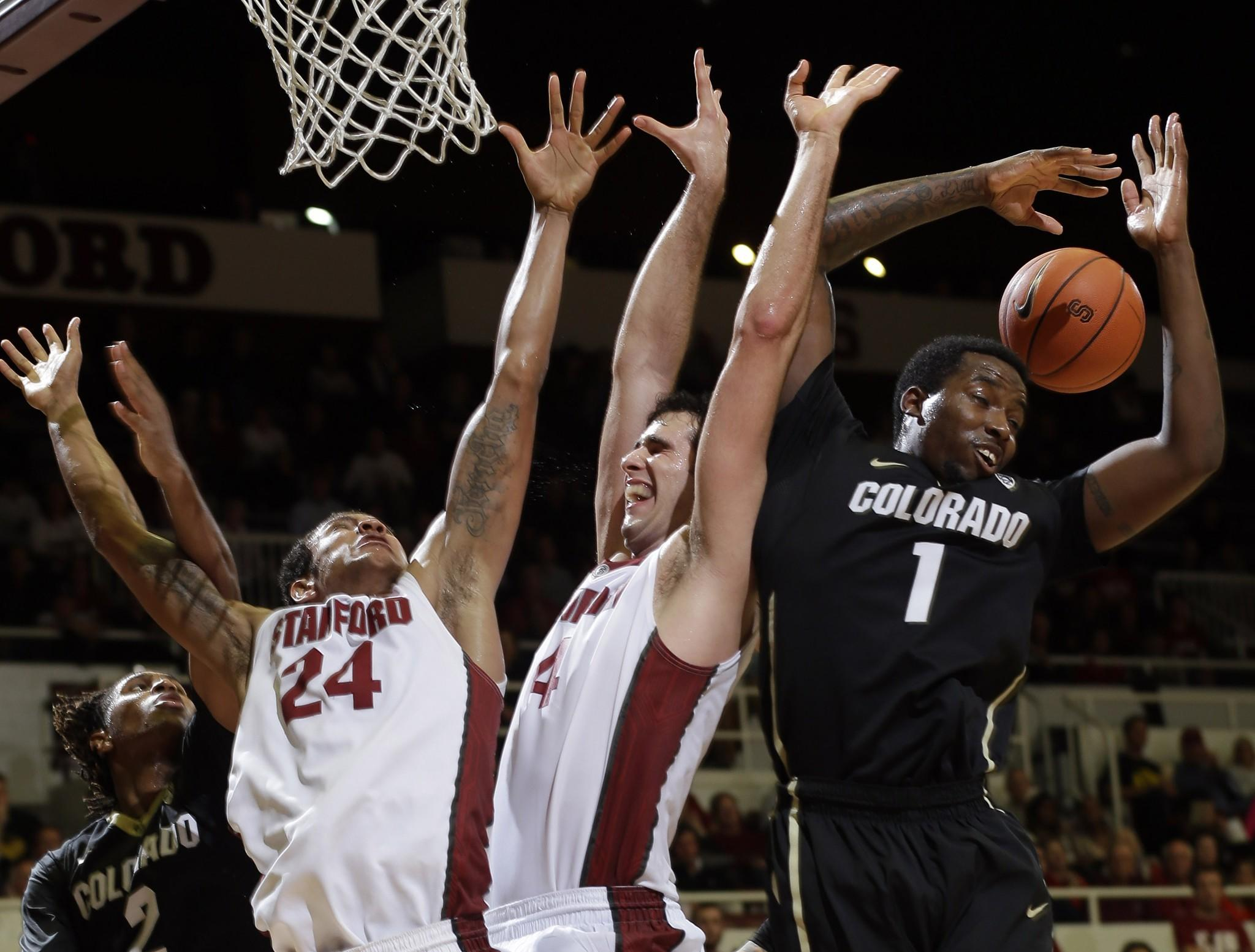 Colorado's Wesley Gordon, right, reaches for a rebound near teammate Xavier Johnson (2) and Stanford's Josh Huestis (24) and Stefan Nastic (4).