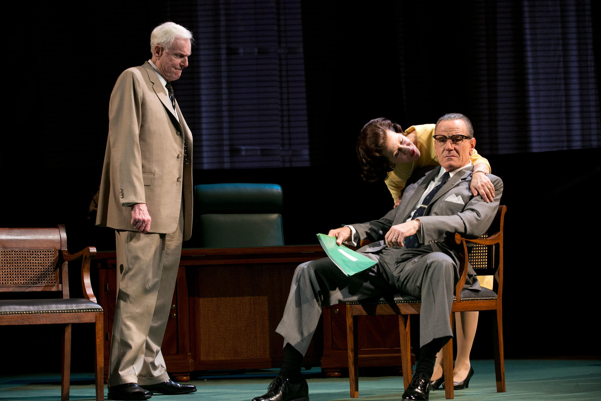 "Bryan Cranston (sitting) playing President Lyndon B. Johnson in the play ""All the Way"" on Broadway. With him are John McMartin as Sen. Richard Russell and Betsy Aidem as Lady Bird Johnson."