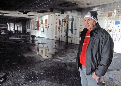 Msgr. Patrick Schumacher inspects fire-damaged Trinity High School in Dickinson, N.D. The Catholic high school's principal has been charged with setting the blaze.