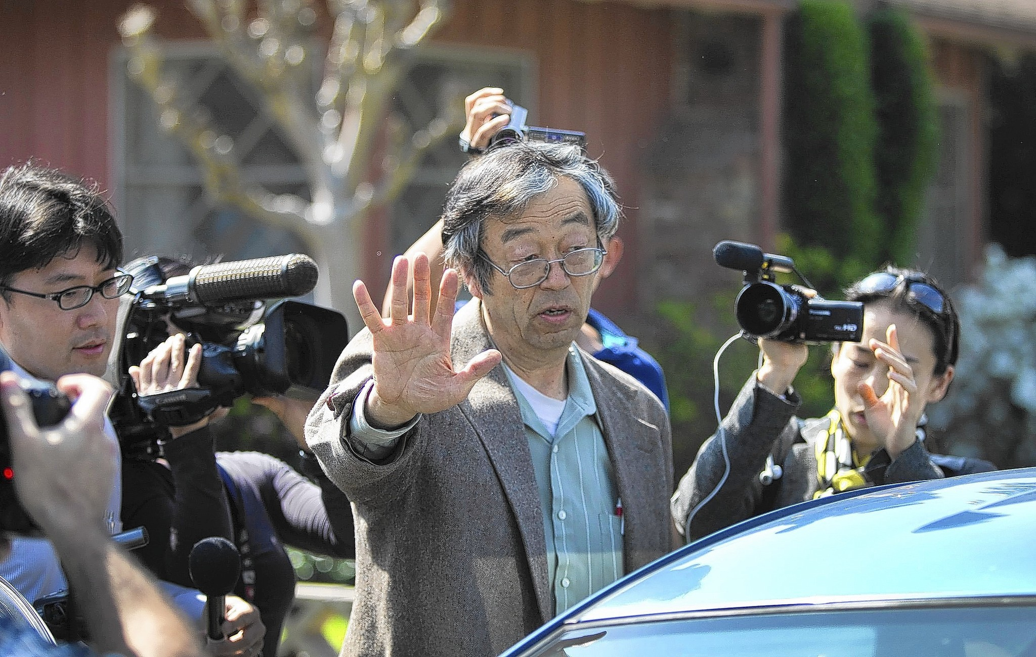 Journalists surround Dorian Satoshi Nakamoto as he emerges from his Temple City house amid a frenzy of speculation that he is the creator of the virtual currency.