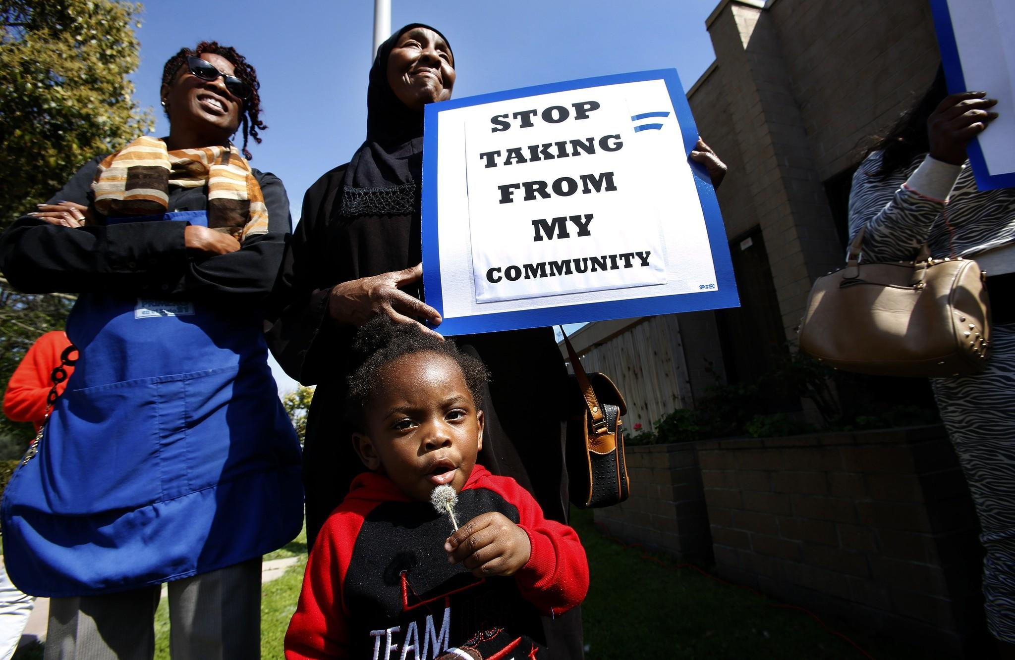 King Street, 2, joins a protest with his great-grandmother Wajeha Bical, holding sign, and others outside the administration building for Kedren Head Start in South Los Angeles. They are unhappy that the community centers may close.
