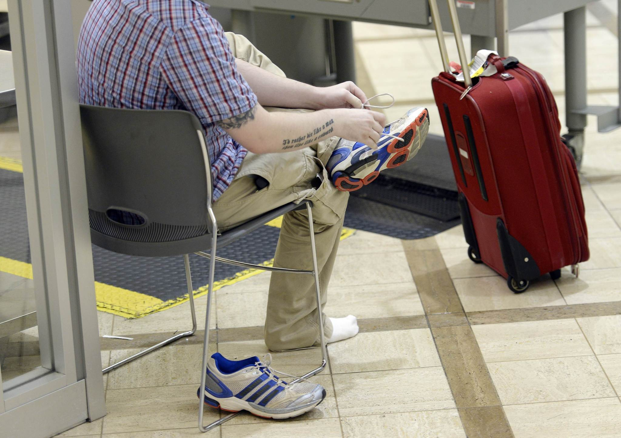 An airline passenger puts on his shoes after passing through TSA security before boarding his flight at Los Angeles International Airport in California on February 20, 2014.