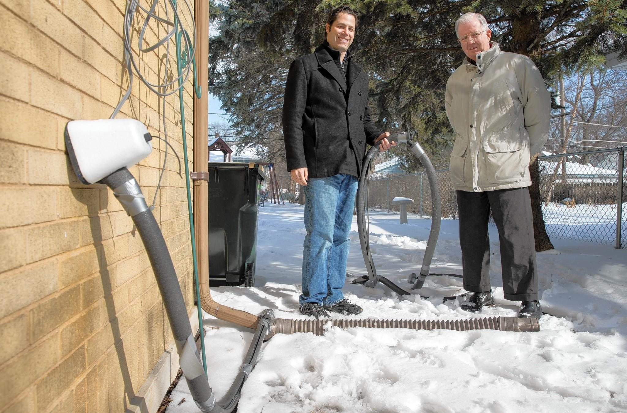 Arlington Heights neighbors Harlan Heiber, left, and Fred Dix show the hose that supplies water to Heiber's house, left, from Dix's home next door. The hose, wrapped in pipe insulation and electrical heating cords, has been pressed into service ever since a water line froze at the end of January.