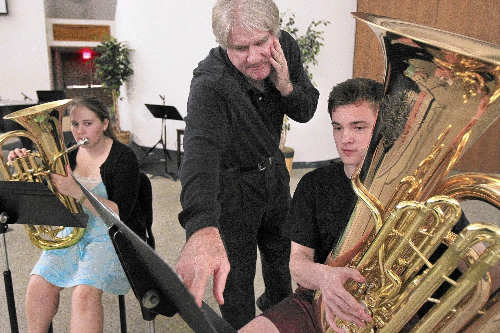 Independent tuba instructor John Van Houten, center, goes over music notes with Concordia Wind Orchestra members Bernard Hoffrogge, 18, and Abby Schneider, 19, during a private lesson at Concordia University in Irvine on Wednesday evening.