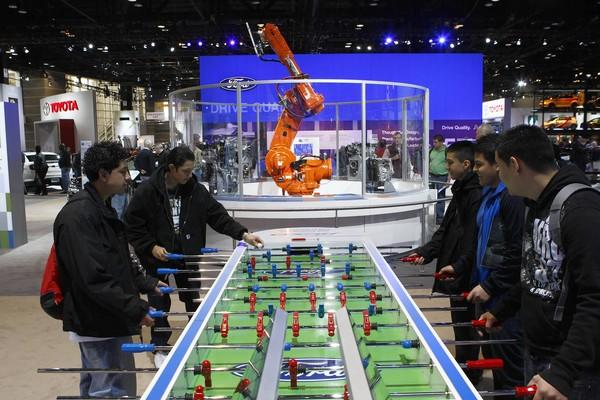 "A robotics demonstration provides a backdrop for a little foosball during the <a class=""taxInlineTagLink"" id=""EVFES0000003"" title=""Chicago Auto Show"" href=""/topic/economy-business-finance/chicago-auto-show-EVFES0000003.topic"">Chicago Auto Show</a> at <a class=""taxInlineTagLink"" id=""PLCUL000061"" title=""McCormick Place"" href=""/topic/jobs-workplace/mccormick-place-PLCUL000061.topic"">McCormick Place</a>."