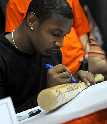 Adam Jones signs a baseball bat for a fan