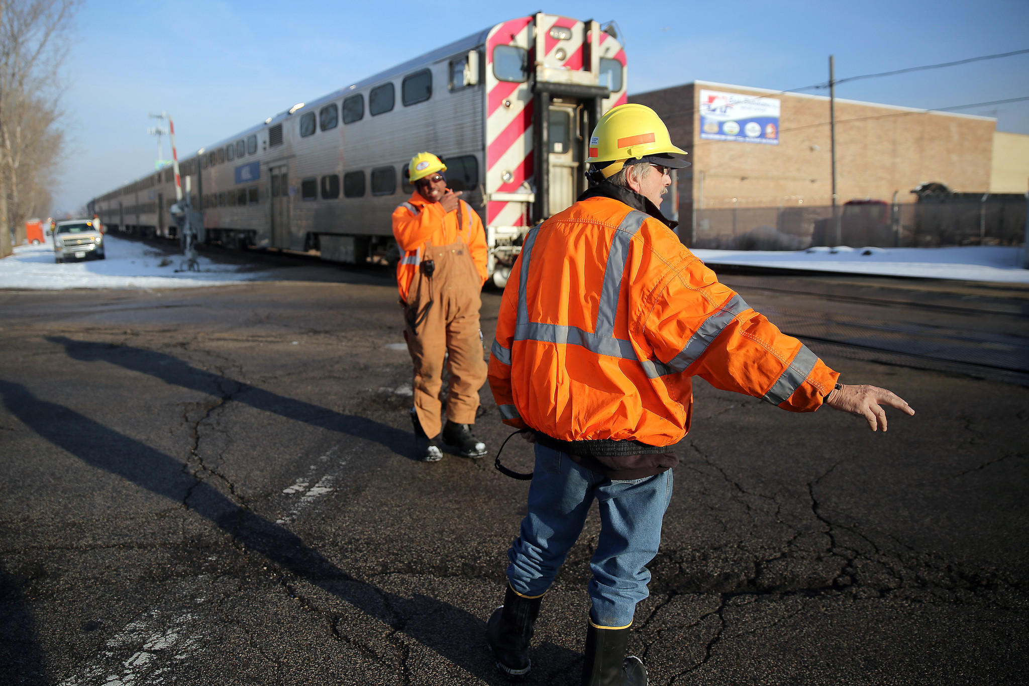 Rail workers stop traffic to allow a train to pass after a pedestrian was struck and killed by an earlier train.