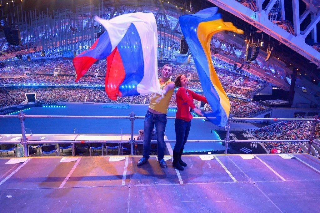Spectators wave Russian and Ukrainian flags ahead of the opening ceremony of the Sochi Paralympic Games.