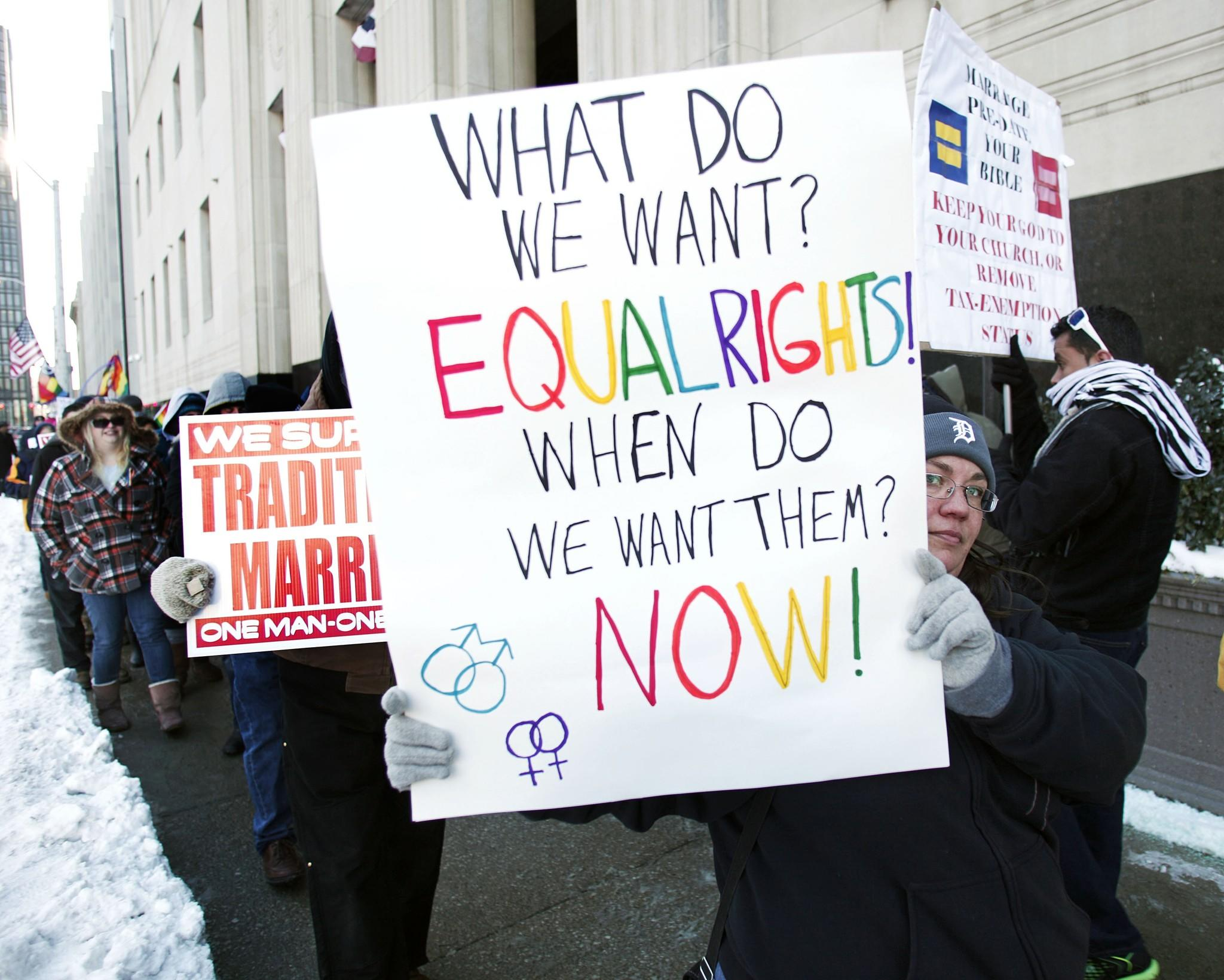 Gay marriage supporters protest next to pro-traditional marriage supporters in Detroit on March 3.