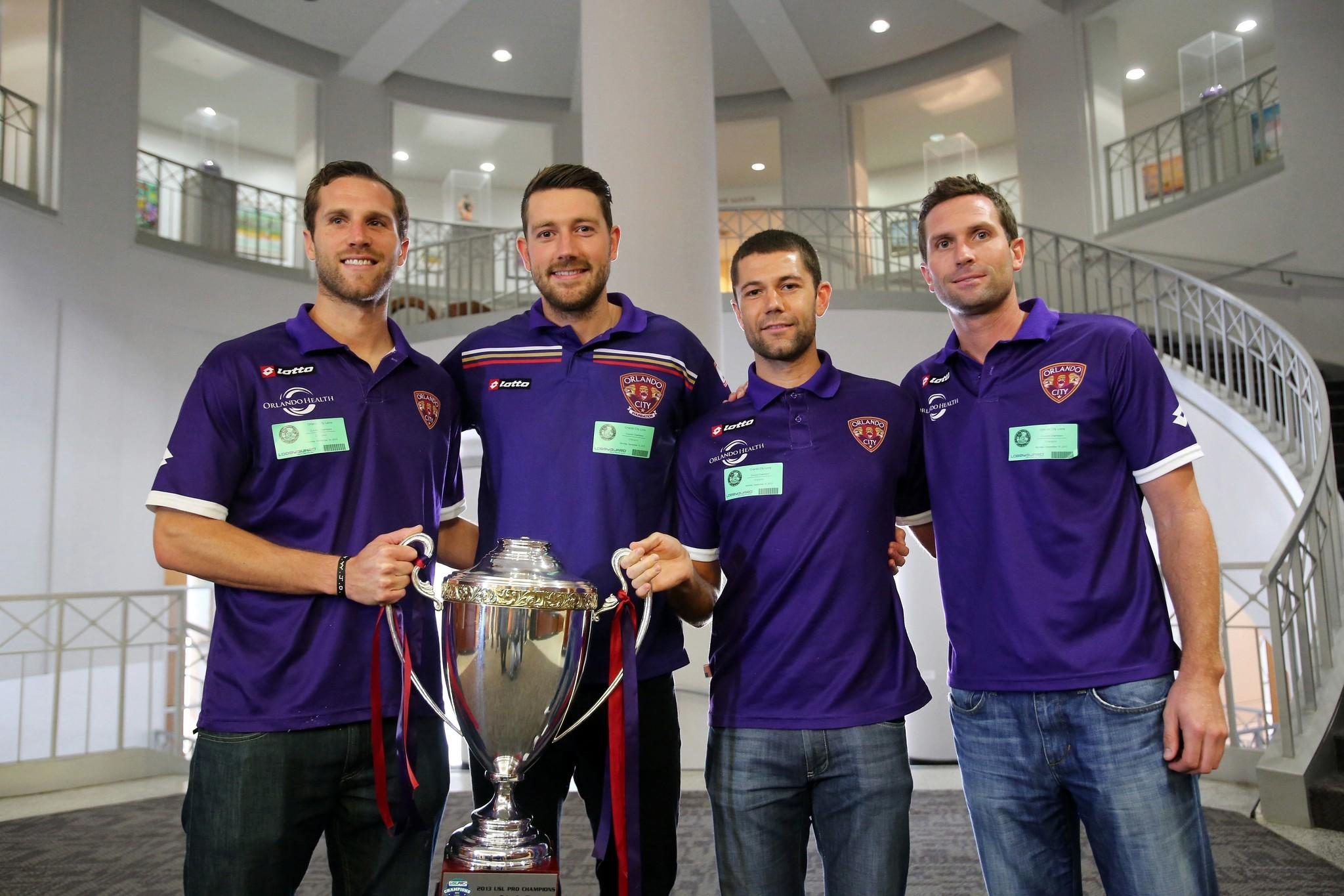 Orlando City Soccer players Rob Valentino, Luke Boden, Anthony Pulis, and Ian Fuller pose for a photo after the Orlando City Council recognized the Lions for their win in the USL Pro Championship, on Monday, September 16, 2013, during a City Council meeting. (Ricardo Ramirez Buxeda / Orlando Sentinel)