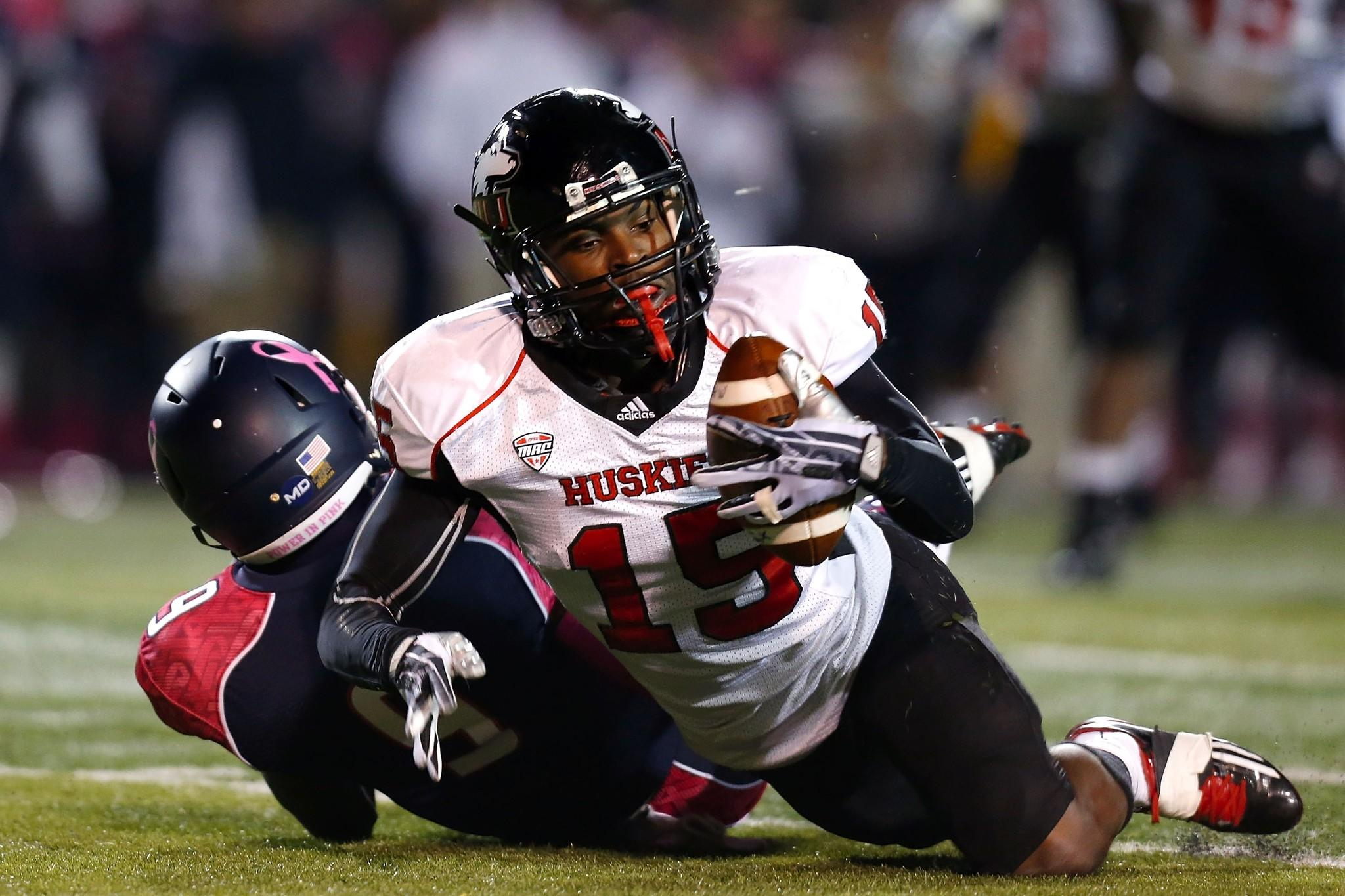 Jimmie Ward (15) of the Northern Illinois Huskies intercepts a pass intended for Alonzo Russell (9) of the Toledo Rockets during the first quarter on November 20, 2013 at the Glass Bowl in Toledo, Ohio.