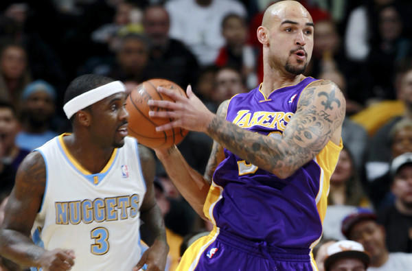 Lakers center Robert Sacre looks to make an outlet pass as Nuggets point guard Ty Lawson heads back on defense in the first half of their game Friday night in Denver.