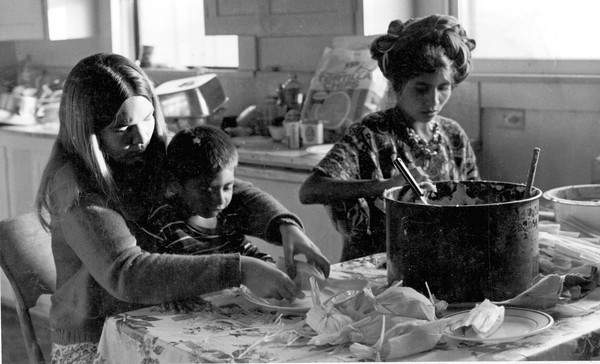 A UCI student learns to make tamales with Maya Weaver Rosa and her son, Machito.