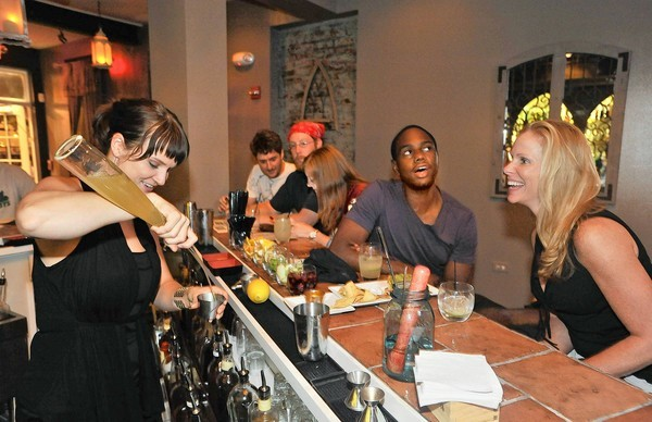 Bartender Megan Deschaine (left) chats with patrons Jason Williams, (second from right), and his companion Lorna Hennessey (right), at Willow in Fells Point.