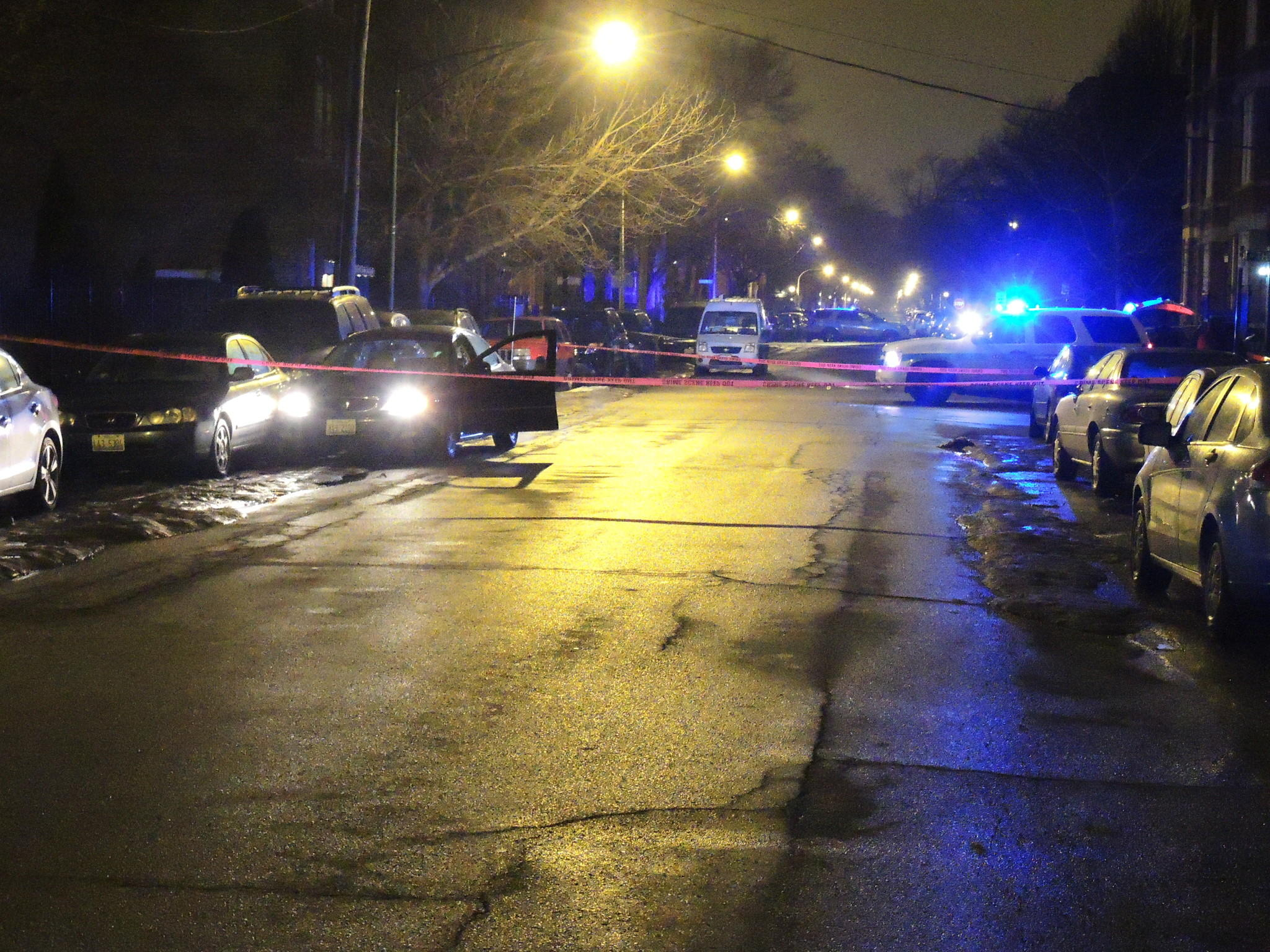 An empty car idles with its door ajar in the 1300 block of West Huron Street early Saturday morning, about an hour after police found a 29-year-old man shot inside a car there.