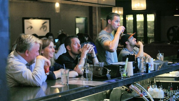 Patrons sit at Townhouse Kitchen's bar, watching sports on the many big screen TVs.