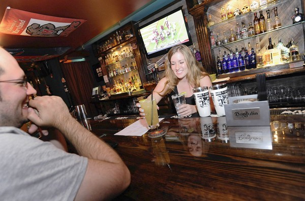 Manager Melanie Hagan, right, serves a margarita verde to Scott Cover at Banditos in Federal Hill.