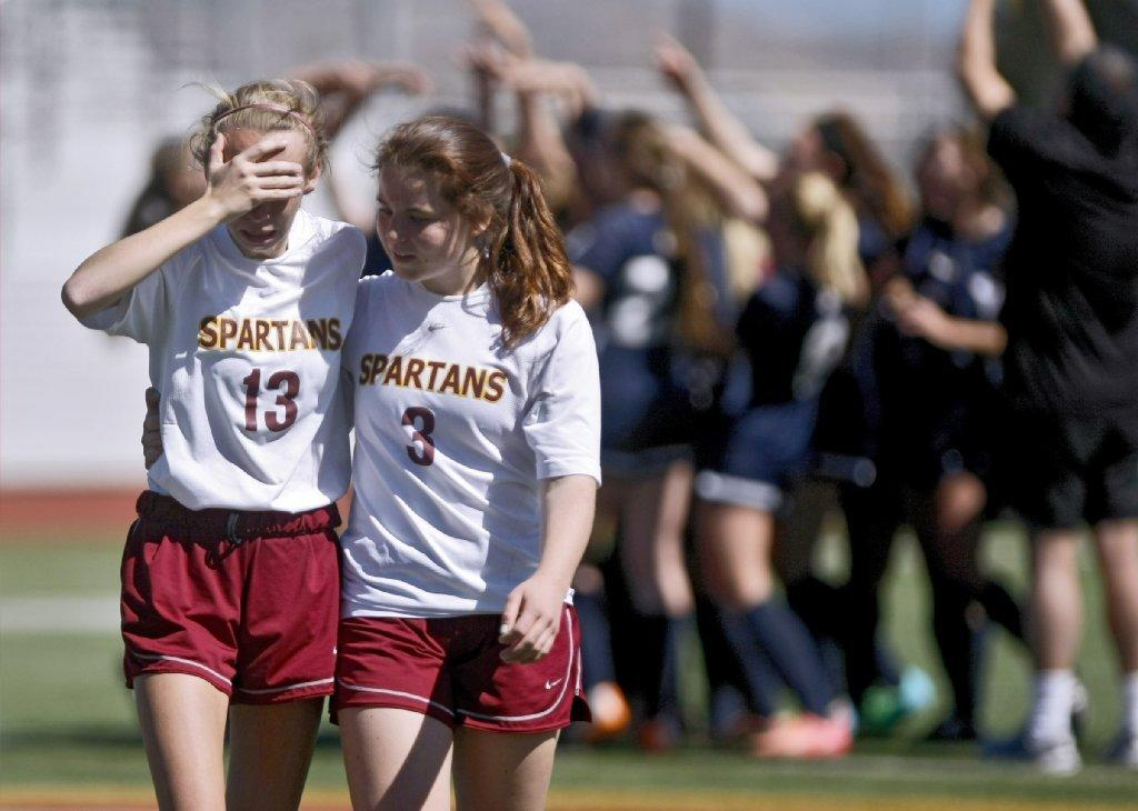 La Cañada High soccer player Kristen Becker (right) consoles Katherine Sheehy after the Spartans lost, 1-0, in overtime in Saturday morning's CIF-SS Division V championship match versus St. Margaret's at Corona High on Saturday. (Raul Roa/Staff Photographer)