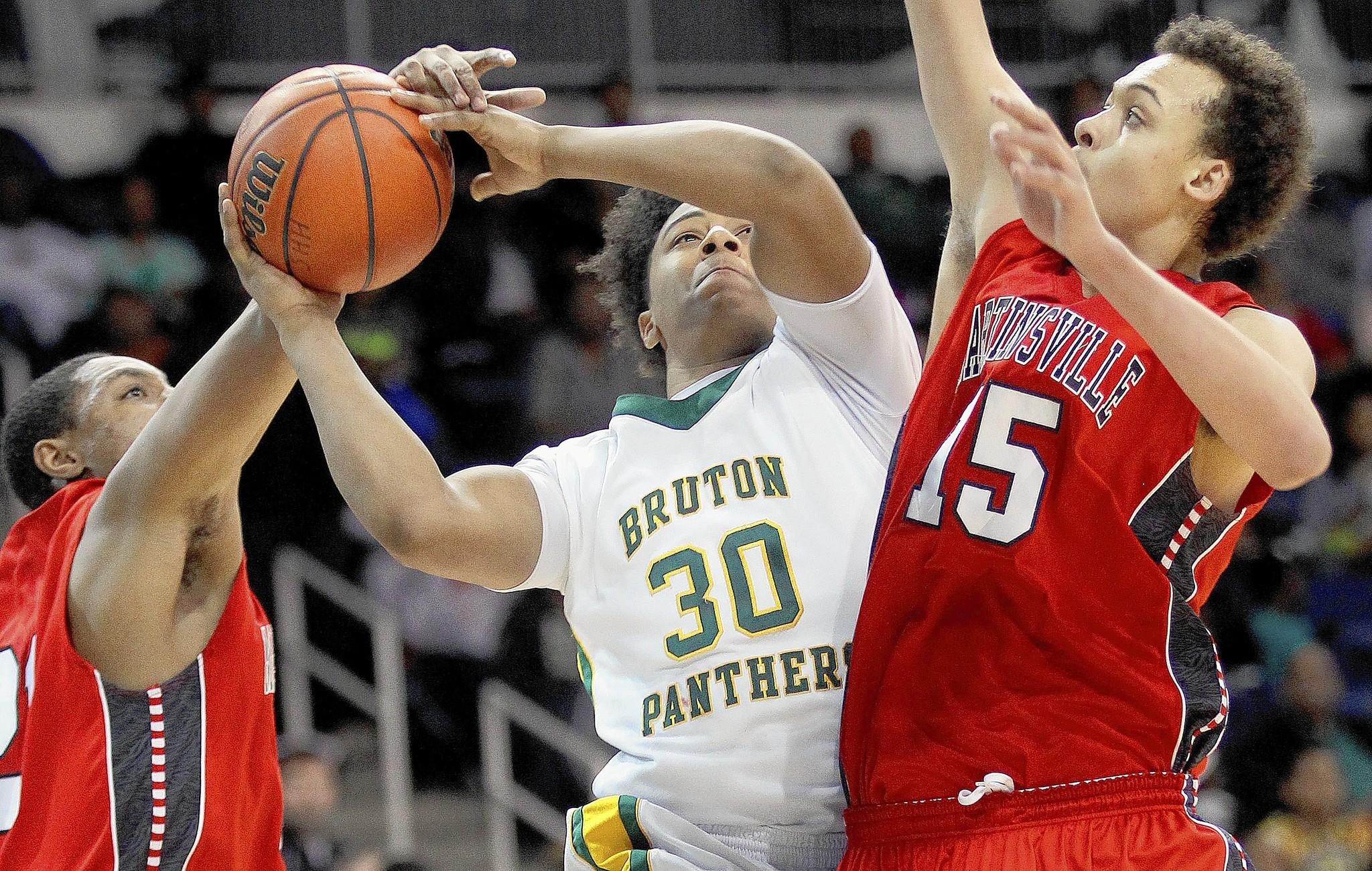 Kapri Doucet of Bruton is fouled by Cameron Turner of Martinsville as he tries to get the shot past Devonnte Holland during the second half of their 2A state semi-final game Saturday in Norfolk.