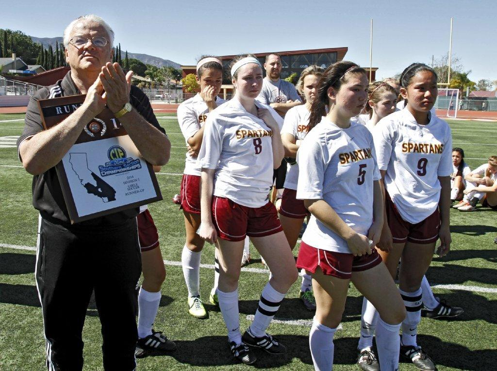 La Cañada High girls' soccer coach Louie Bilowitz holds the runner-up trophy after his squad played in the CIF-SS Girls Division V championship match versus St. Margaret's at Corona High on Saturday. The Spartans lost, 1-0, in overtime on a penalty kick. (Raul Roa/Staff Photographer)