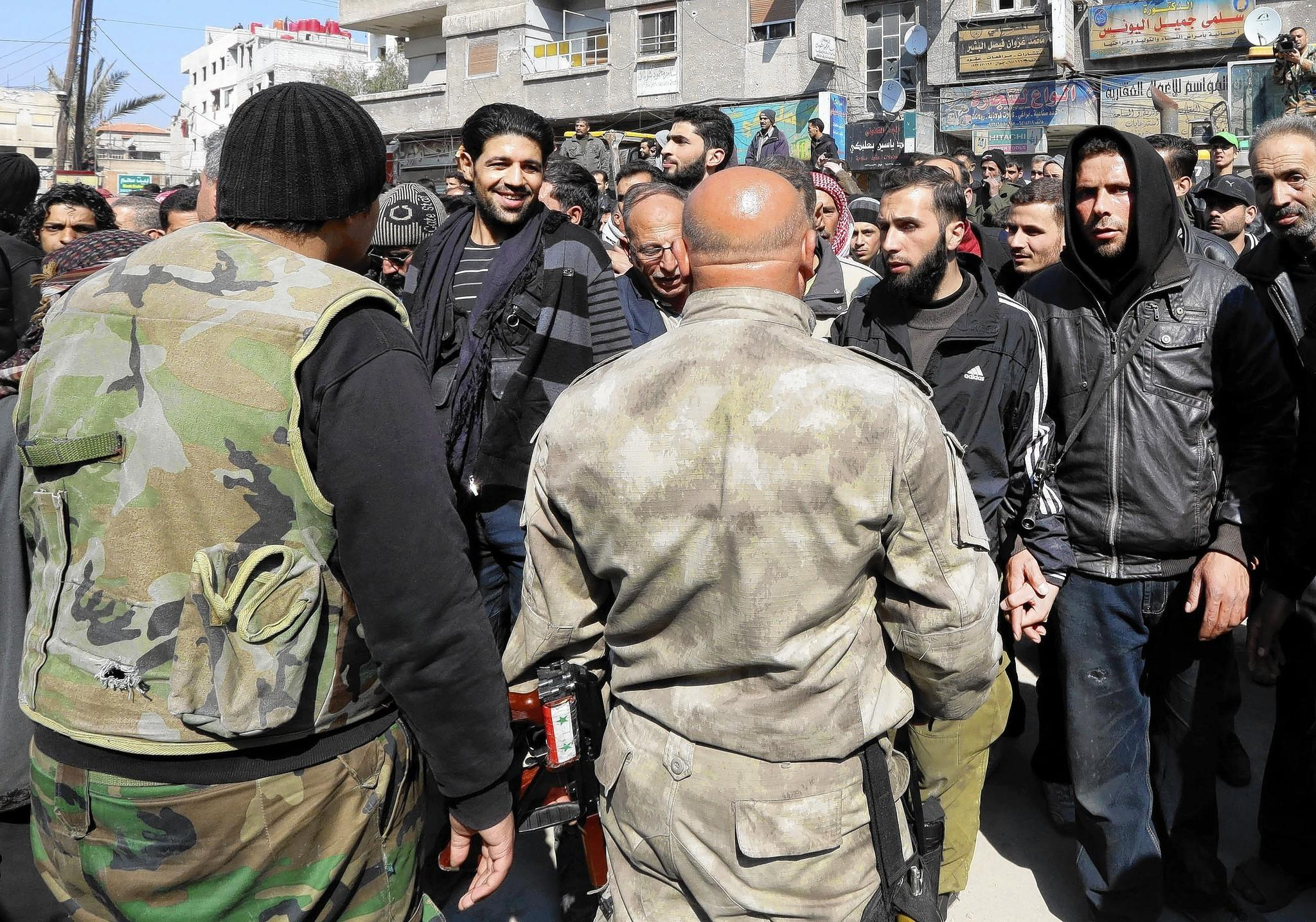 Syrian rebels, in the background, talk with Syrian government forces last month after a reconciliation agreement between the two groups in Babila, on the outskirts of Damascus.