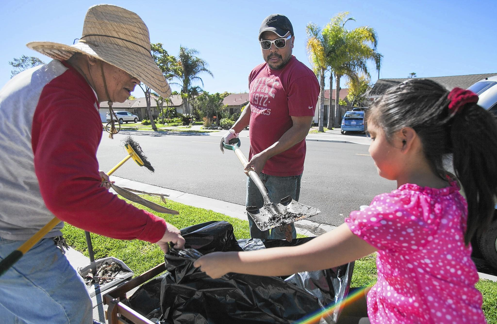 Carlito Franco, left, and Guadalupe Martinez, hold a bag open for Temo Martinez as he scoops up dirt from the curb during a city-sponsored community clean-up day in Costa Mesa on Saturday.