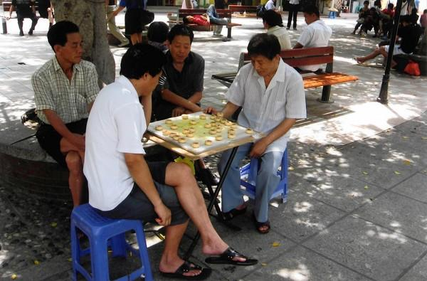 Men play a xiangqi in the park on Gulangyu Island.