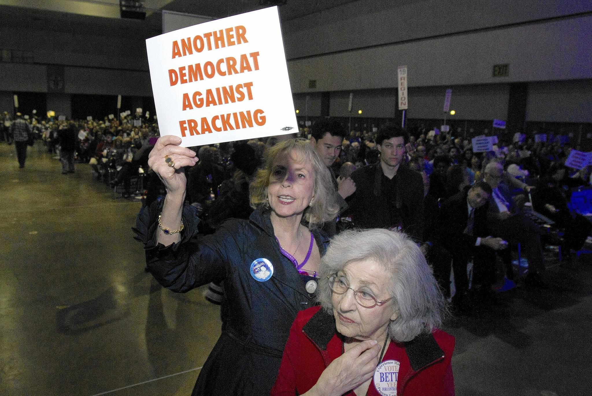 Cindy Asner, left, and Leah Herzberg -- who oppose the oil extraction method known as hydraulic fracturing, or fracking -- hold up signs as Gov. Jerry Brown speaks at the California Democratic Convention in Los Angeles.