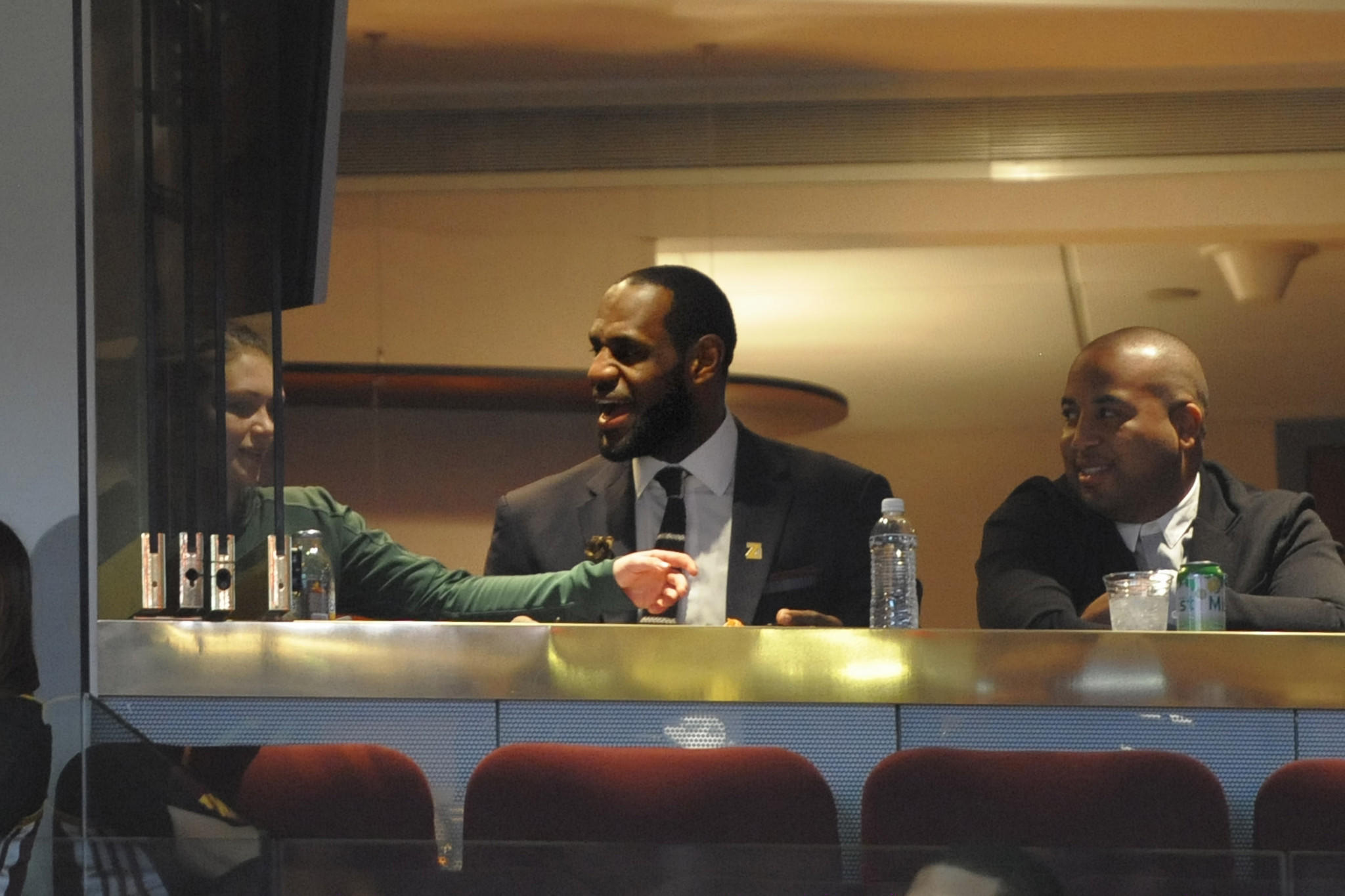 Miami Heat superstar LeBron James, center, sits in a suite during a game between the Cleveland Cavaliers and the New York Knicks at Quicken Loans Arena.