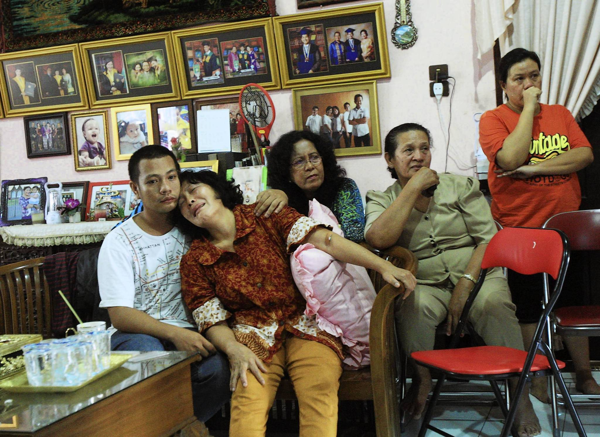 Relatives of a passenger on the missing Malaysia Airline plane watch television for updates in Medan, Indonesia, on Sunday.