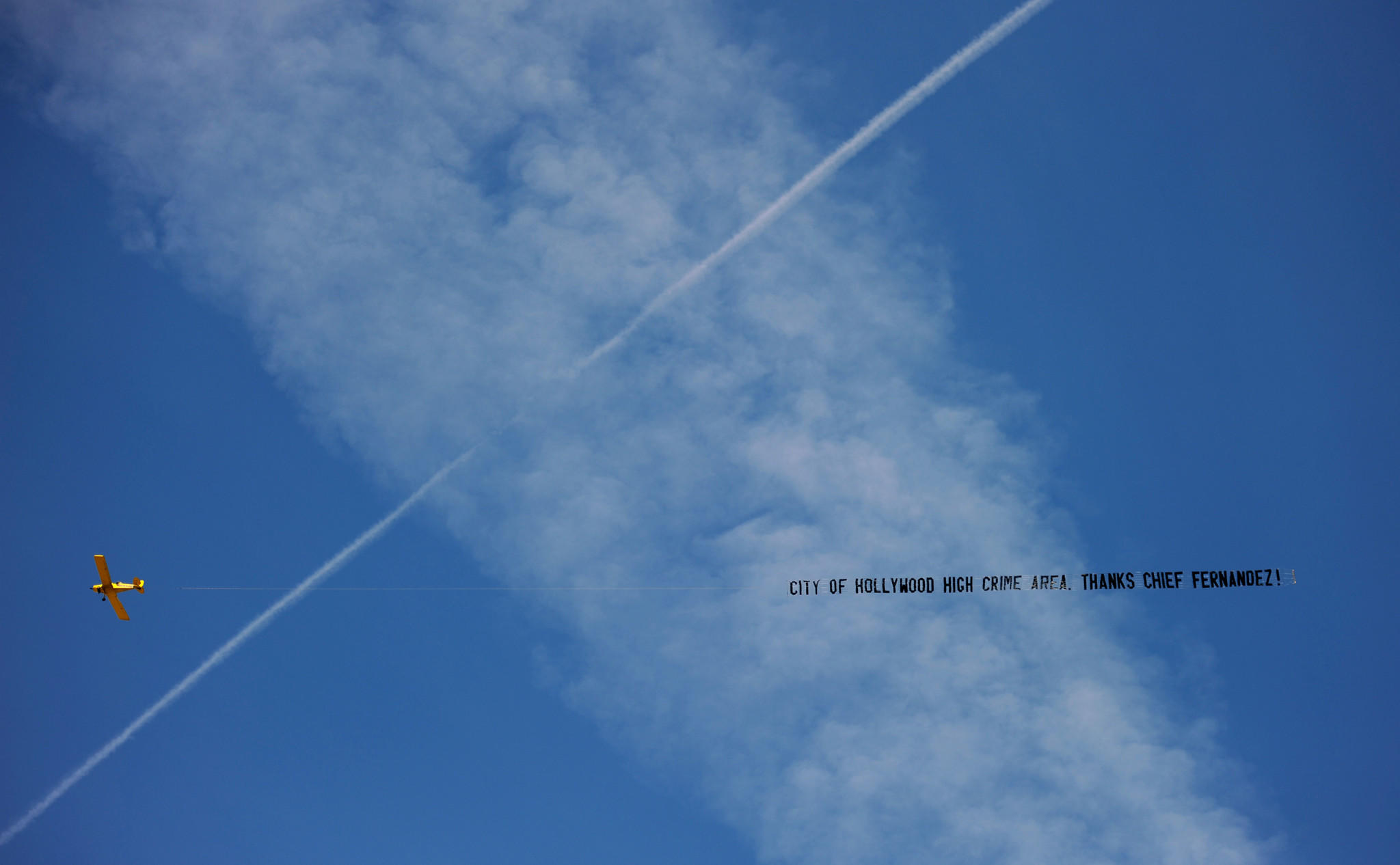 A plane carrying a banner warning of high crime in Hollywood flew over the beach and downtown Hollywood on Sunday. The banner, paid for by the police union, blames it all on the chief.