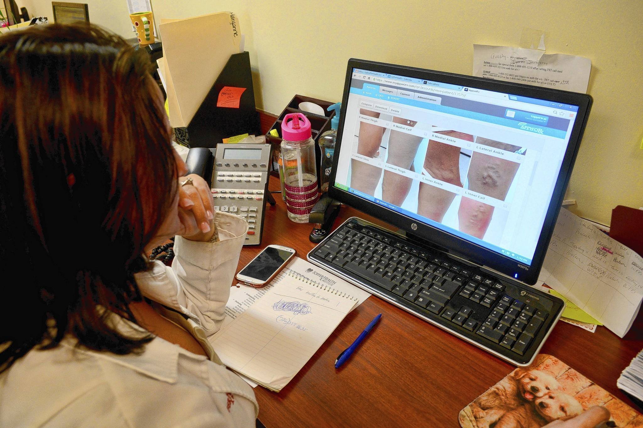 Soffer Health Institute office manager Tainet Gonzalez looks at a patient's photographs using the AppwoRx website.