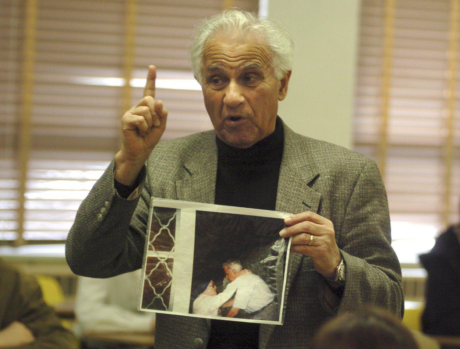 Leo Bretholz, an Holocaust survivor, speaks to students at the John Carroll School in Bel Air. He is showing a picture of himself and Sister Jeanne D'Arc when they were reunited in 1999 in France. Sister Jeanne D'Arc had helped him in 1944 when he was rushed to St. Vincent's Hospital in France for emergency surgery