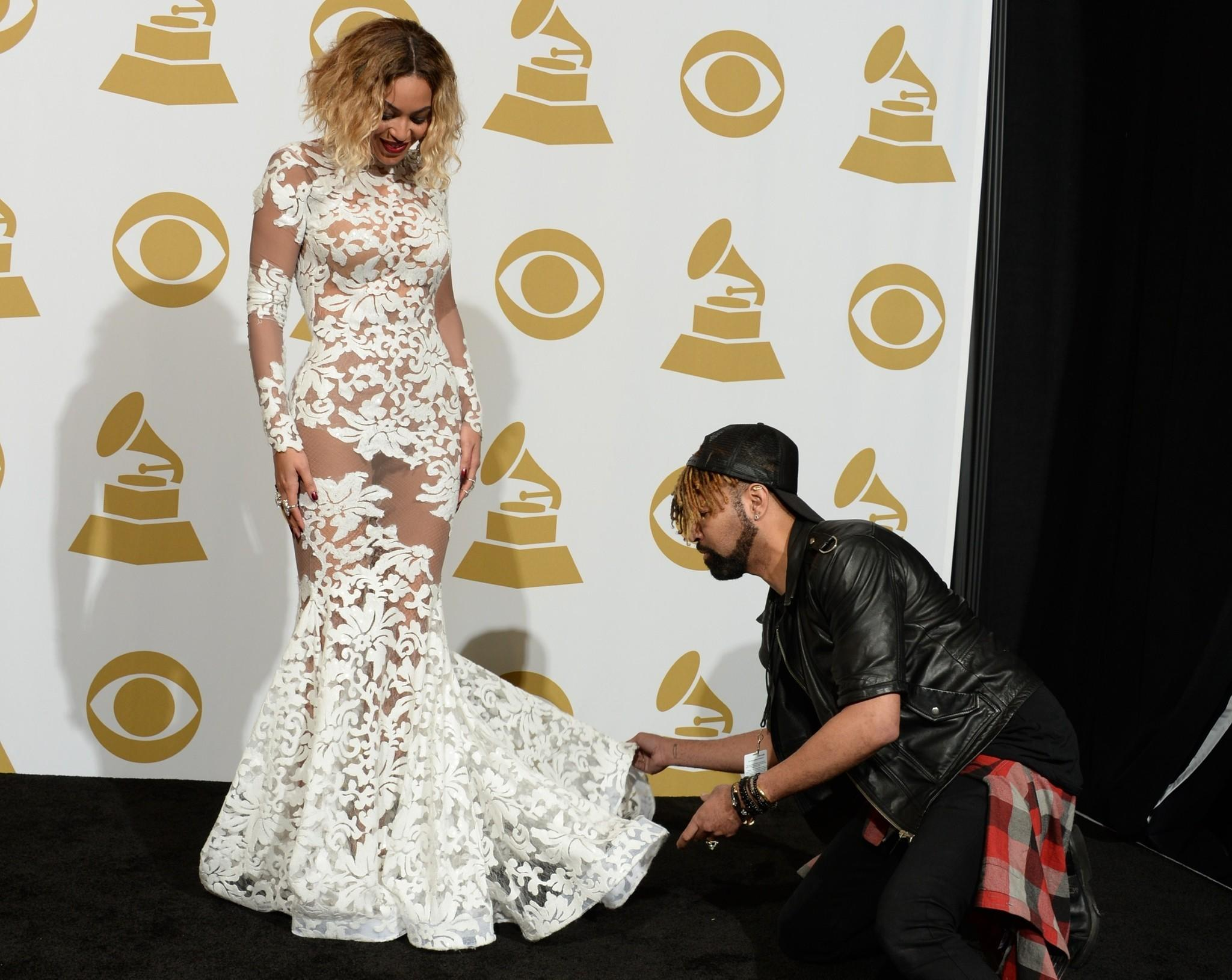 Beyonce gets some help arranging her gown in the press room at the 56th Grammy Awards.
