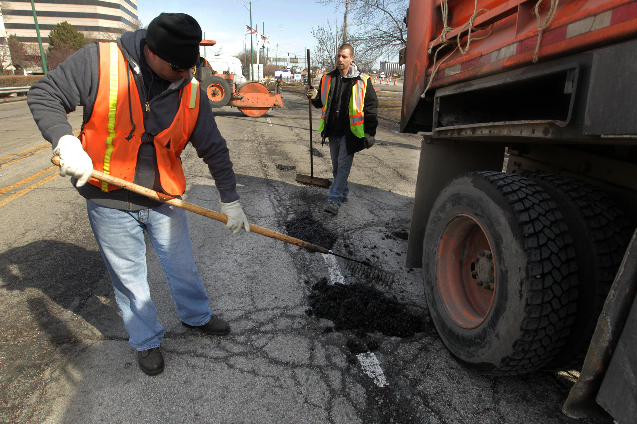 """Chicago Dept. of Transportation workers fill in potholes in the 8400 block of West Bryn Mawr today. Mayor Rahm Emanuel ordered """"strike teams"""" to work in geographical grids on Chicago arterial streets over the next several weeks."""