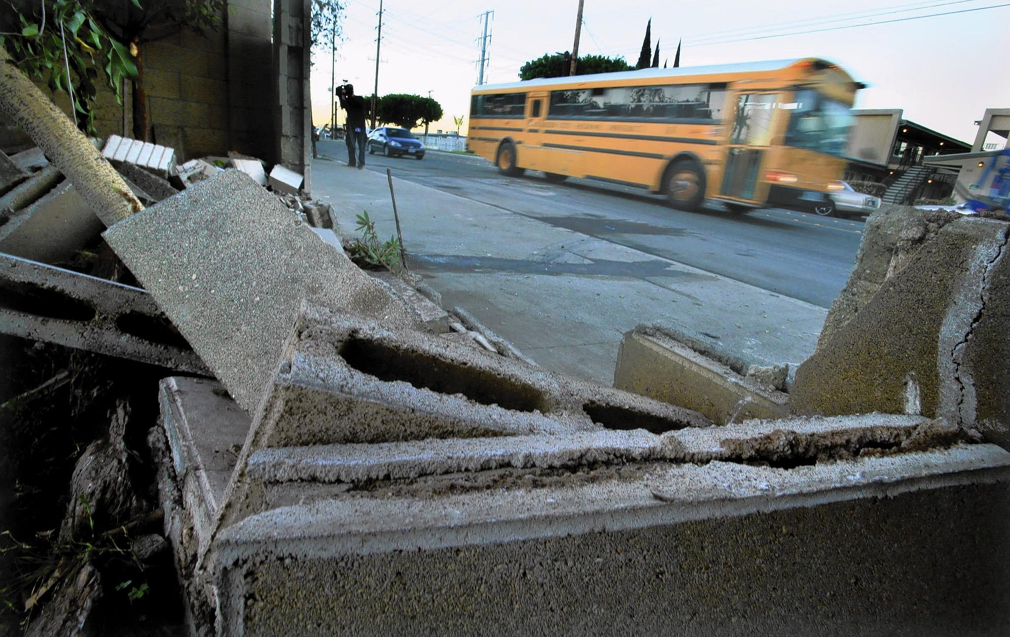 A school bus drives past the scene of a crash near the intersection of East and South streets in Anaheim that left two people dead and one injured Sunday.