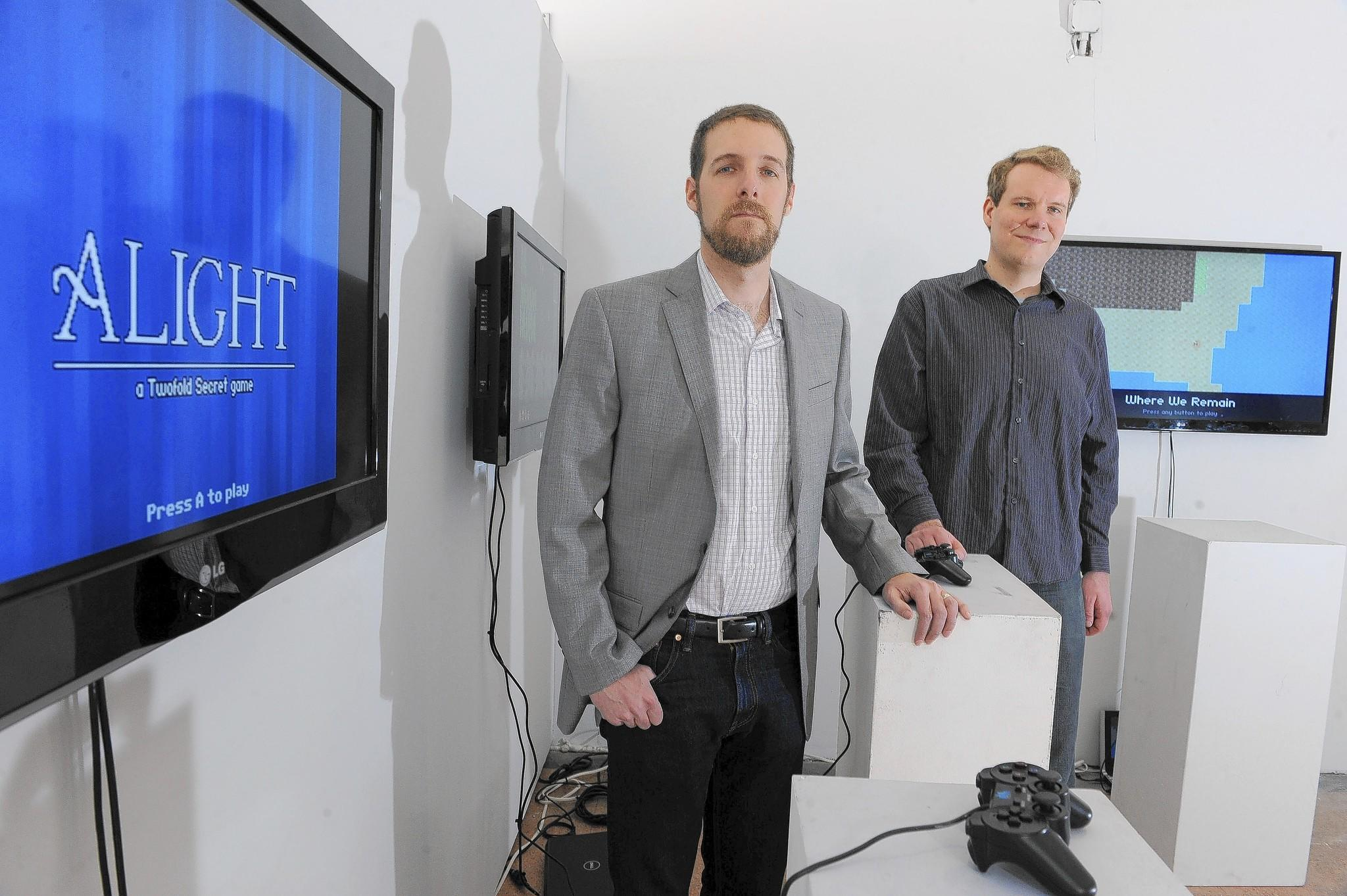 Joel Haddock, left, and Chris Klimas, partners in the independent video game company Twofold Secret, pose at an exhibition of their games at Current Space.