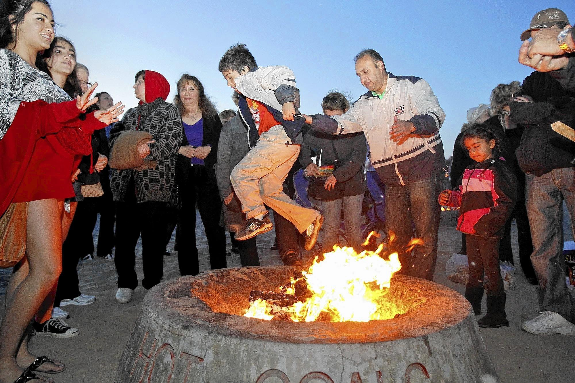 Kianoush Hamadani, center right, of Irvine, helps his son Cameron over a bonfire in celebration of the Persian New Year, know as Norooz, held at Corona del Mar State Beach in 2012.