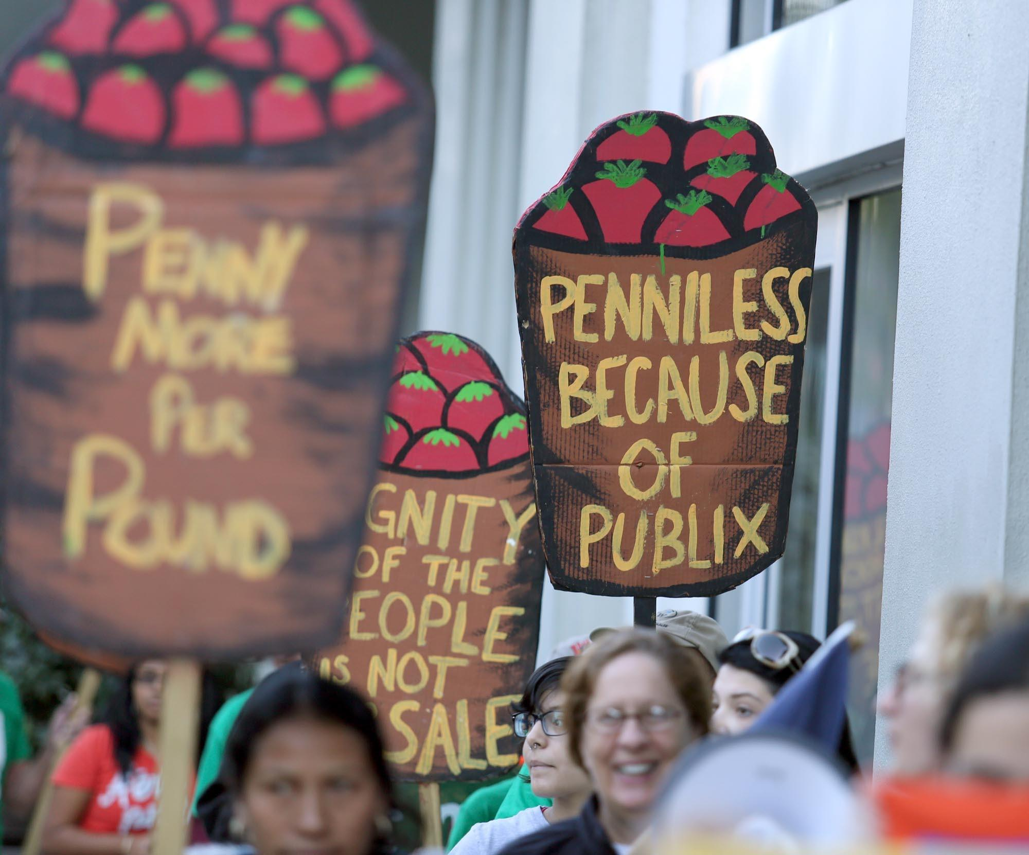 Protesters carry signs during a protest outside the Publix supermarket on Saturday, February 2, 2013. The protest was staged by farmworkers activists in an attempt to raise wages for tomato pickers.
