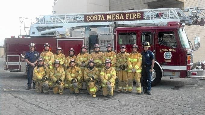 The 13 graduates of the Costa Mesa Fire Explorers Post 400 program gather for a photo.
