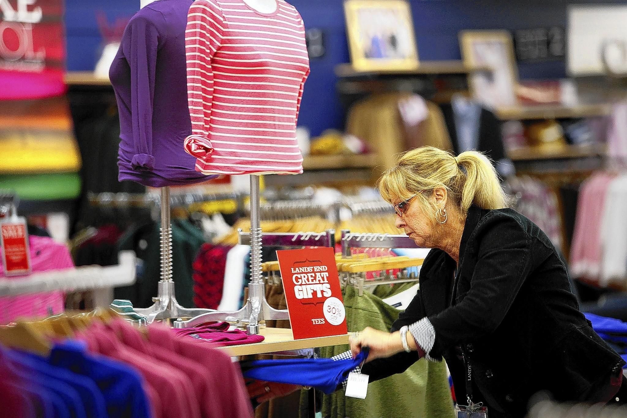 A Lands' End employee organizes apparel at a store in Torrance, Calif. Though the company's spinoff date from Sears Holdings Corp. isn't set, Lands' End will pay Sears a cash dividend of $500 million before the spinoff, financed by a new term loan.