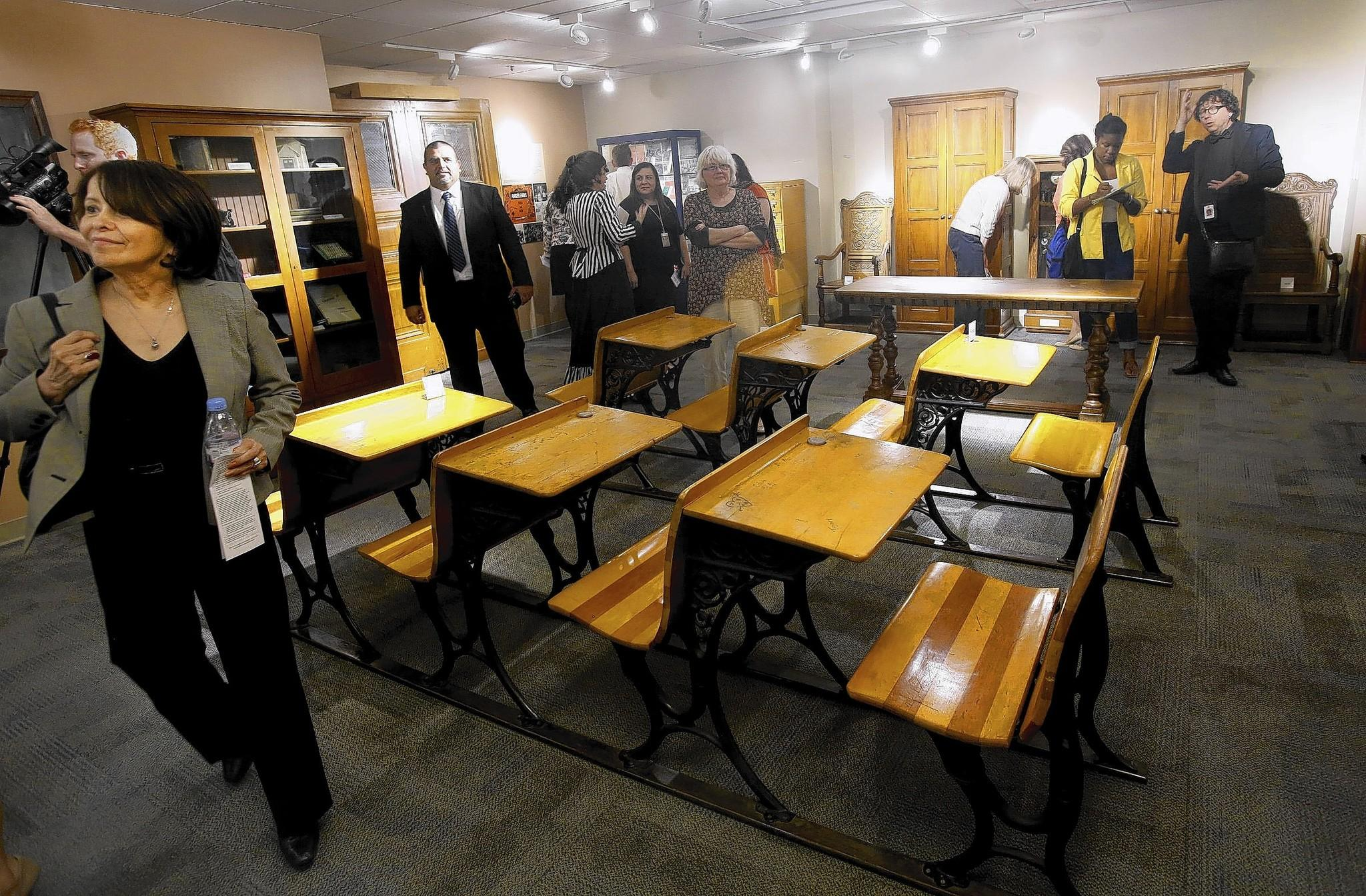 Visitors check out L.A. Unified's Heritage House exhibit at district headquarters downtown. The desks are from early era of the district.